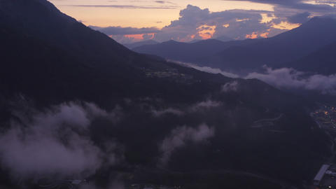 Clouds over city in mountain valley from drone above. Aerial view cloudy sky at evening sunset in Archivo