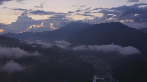Clouds over city in mountain valley from drone above. Aerial takeoff view cloudy sky at evening Archivo