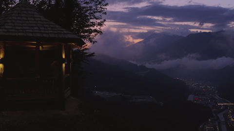 Evening sunset in mountain city. Aerial view cloudy mountain at twilight. Tourist people on Footage