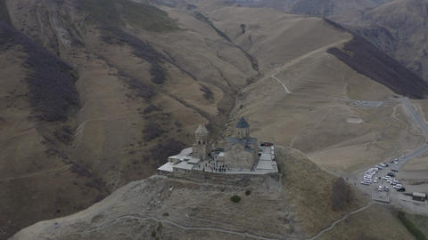 Aerial around landing view ancient georgian church on highland on Kazbek mountain. Old orthodox ビデオ