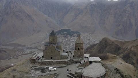 Aerial flying around view ancient georgian church on highland on Kazbek mountain. Old orthodox Live Action