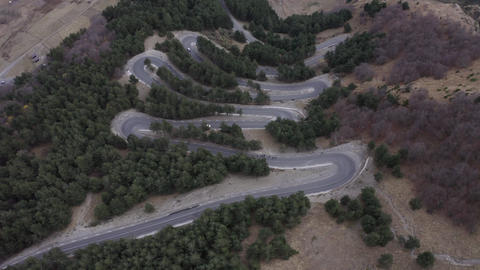 Aerial top view winding car road in mountain. Drone view city architecture in mountain valley. Car Live Action
