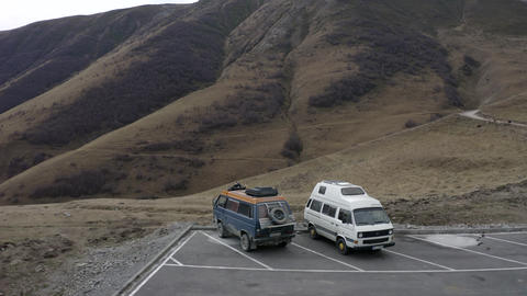 Aerial view minivan rv transporter vw cars on parking lot on mountain background. Drone view mini Live Action