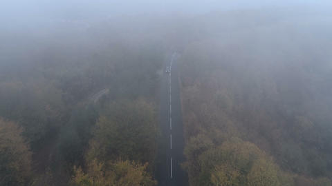 Aerial view of black SUV with turned headlights driving along spooky foggy road ビデオ