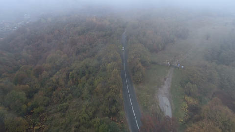 Drone follows white car driving on foggy mountain road in the autumn Archivo