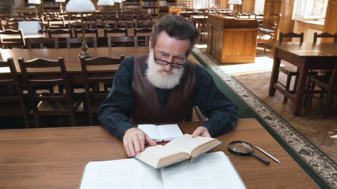 Attractive focused on reading bearded old man with glasses sitting at the Footage