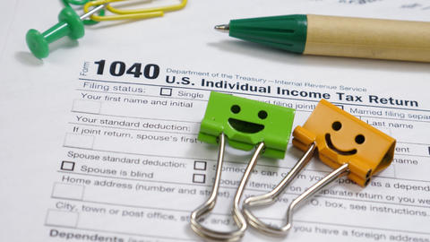 Smiles Binder Clips and Pen on 1040 Tax Form Live Action