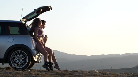 Two young women watch to the sunset in the mountains by sitting in the car trunk Footage