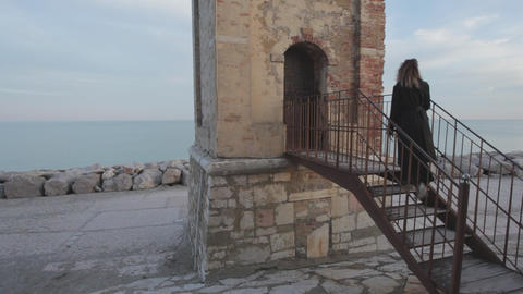 Woman with black dress enter in a bell tower with the sea on the horizon Footage