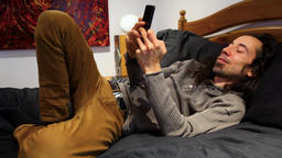 Man on his cellphone in bed Live Action