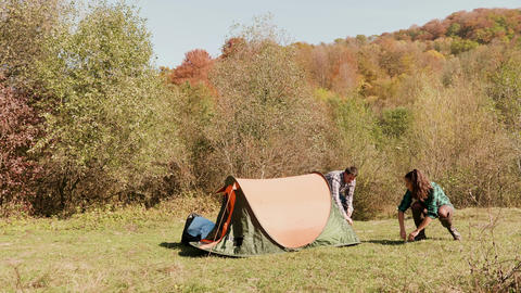 Beautiful young couple helping each other setting up the camping tent Footage