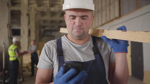Portrait of adult Caucasian builder in white helmet laughing out loud as looking Footage