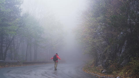 Carefree Confident Man walking along a deserted road in the mist and fog Footage