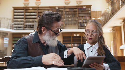 Pretty teen schoolgirl with glasses showing how to use ebook to her respected Footage