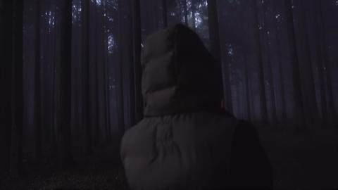 Lost person concept. Tourist lost in deep woods in the night looking for mobile Live Action