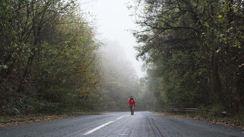 A confident man walks alone on lonely road in the forest Footage