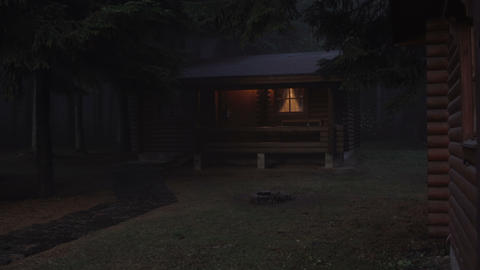 Glowing windows on log cabin in foggy pine forest. Horror, spooky concept ライブ動画