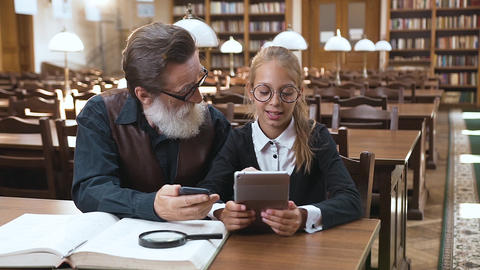 Pretty blond teen schoolgirl holding ebook in her hands and talking with her Footage
