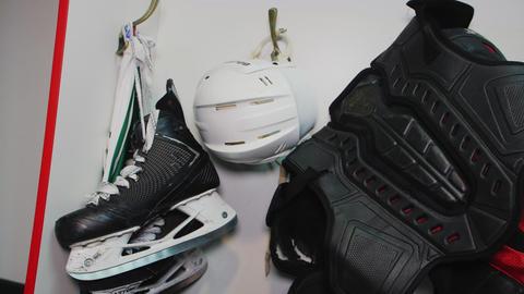 hockey skates helmet and protective vest hang in team room Footage