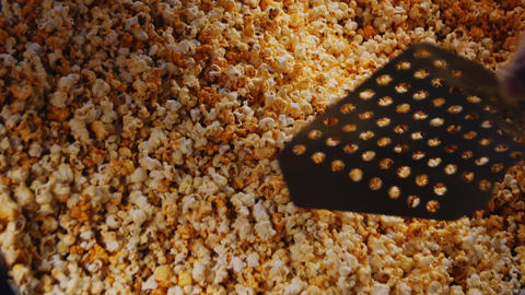 person mixes tasty fresh popcorn in fastfood cafe closeup Live Action