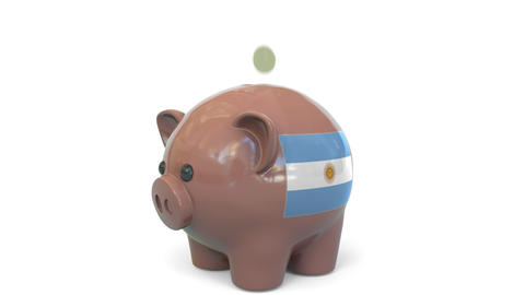 Putting money into piggy bank with flag of Argentina. Tax system system or Live Action