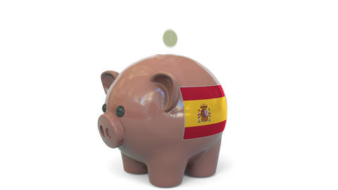 Putting money into piggy bank with flag of Spain. Tax system system or savings Live Action
