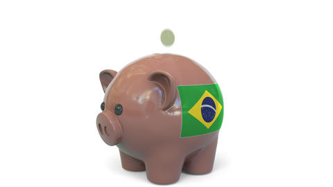 Putting money into piggy bank with flag of Brazil. Tax system system or savings Live Action