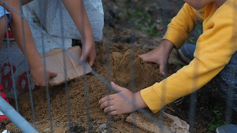 Boy and girl making a sand castle in construction zone Footage