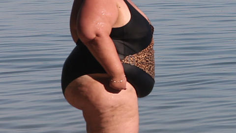 Women with overweight standing in a swimsuit at the water surface Footage