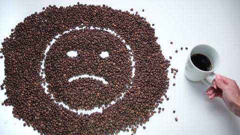 Sad smiley made of coffee beans becoming happy Footage