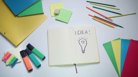 Word Idea and light bulb written on white note pad Footage