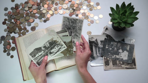 Woman looking at old photos on the table Footage