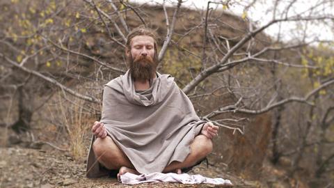 Yogi asket meditating on nature Footage
