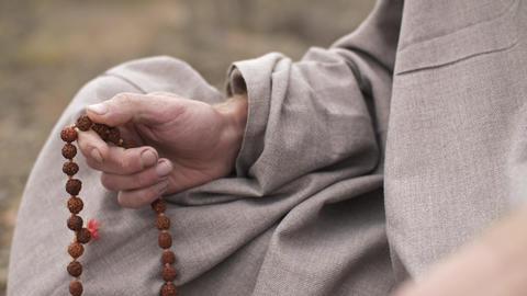 Hindu man meditating with beads ビデオ