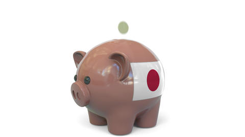 Putting money into piggy bank with flag of Japan. Tax system system or savings Live Action