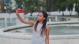 Cheerful african girl taking selfie in front of fountains Footage