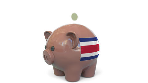 Putting money into piggy bank with flag of Costa Rica. Tax system system or Live Action