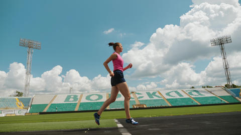 Young athletic girl runs on running track ビデオ