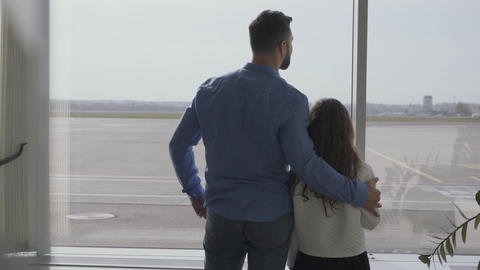 Back view of adult Caucasian man standing with little girl in the airport and Footage