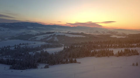 Flight over Carpathian mountains in winter at sunrise. Rural landscape in winter Live Action