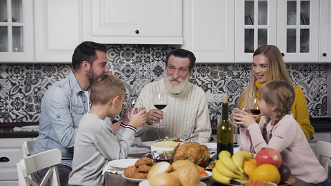 Good-looking happy family sitting at the festive table with tasty meals and Footage