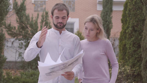 Male Caucasian bearded constructor showing architectural drawings to the Live Action