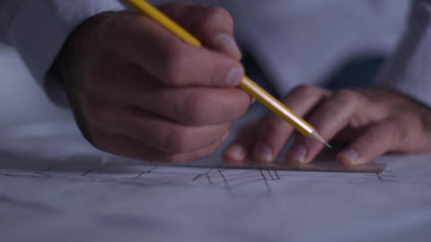 Close-up of male Caucasian hands drawing blueprint. Adult architect in the Footage