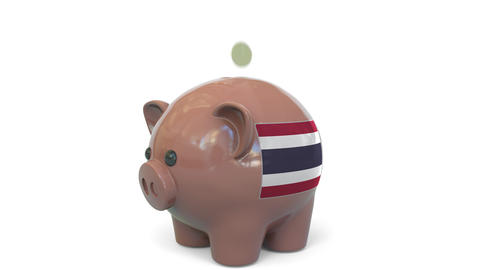 Putting money into piggy bank with flag of Thailand. Tax system system or Live Action