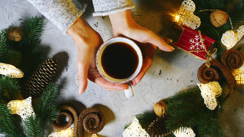 Christmas is a family holiday. Beautiful female hands put a cup of black tea or Live Action
