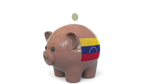 Putting money into piggy bank with flag of Venezuela. Tax system system or Live Action