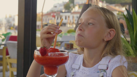 Portrait teenager girl drinking strawberry cocktail by straw in outdoor summer GIF