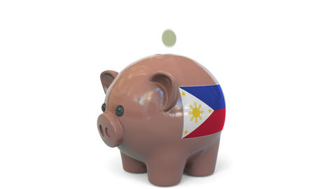 Putting money into piggy bank with flag of Philippines. Tax system system or Live Action