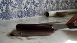 Homemade culinary artisan tempering smooth dark chocolate confectionery on marbl Footage
