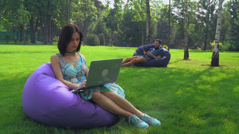 The girl brunette sits in a chair in the park and working on a laptop Footage